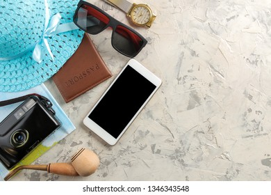 Travel concept Smartphone, passport, map, photo chamber and sunglasses on a light concrete background. top view