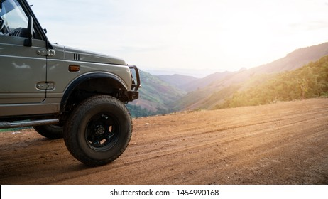 Travel concept with sunset and mountains. Closeup photo of offroad wheel. Off-road travel on mountain road. Offroad car concept with mountains.Off-road travel on mountain road.