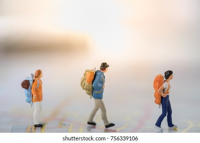 Travel Concept. Three traveller miniature figures with backpack walking on street map.