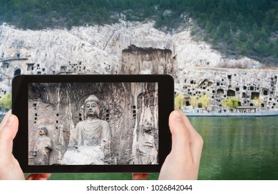 travel concept - tourist photographs Buddha statue on West Hill of Chinese Buddhist monument Longmen Grottoes (Longmen Caves) from the east bank of the Yi River in spring season on tablet