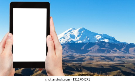 travel concept - tourist photographs of Mount Elbrus from Bermamyt Plateau at autumn morning in North Caucasus mountains of Russia on smartphone with cut out screen with blank place for advertising