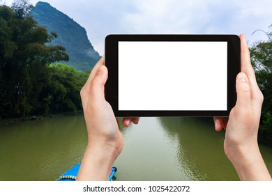 travel concept - tourist photograps river in Yangshuo county in China in spring morning on tablet with cut out screen for advertising logo
