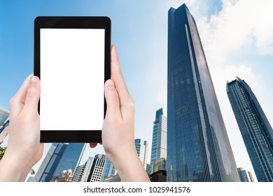 travel concept - tourist photograps skyscraper in Zhujiang district of Guangzhou city in China in spring morning on tablet with cut out screen for advertising logo