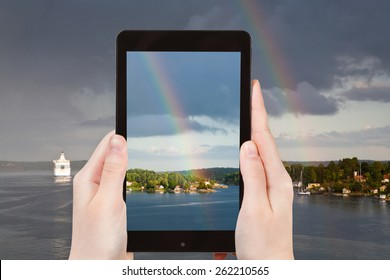 travel concept - tourist takes picture of rainbow over small village on Baltic sea coast on smartphone, Sweden