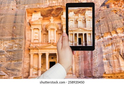 travel concept - tourist taking photo of Treasury Monument and plaza in ancient city Petra on mobile gadget, Jordan