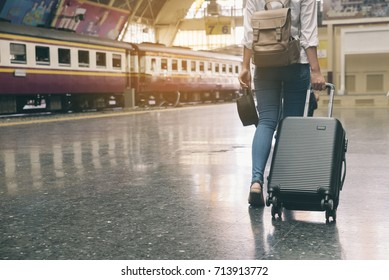 Travel concept.At train station, Young Tourist Girl walking and Dragging luggage suitcase bag and searching hotel at platform. Asian women waiting for train and planning happy holiday vacation.
