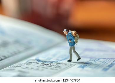 Travel Concept. Traveler miniature figure walking on passport with immigration stamps.