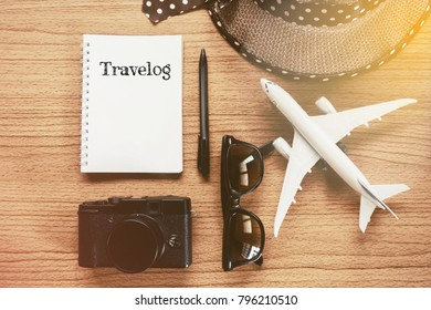 Travel concept - TRAVELOG word written on notepad. Traveller object on woodden desktop