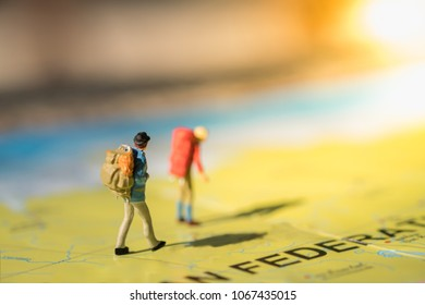 Travel Concept. Two traveler miniature figures with backpack walking on world map.