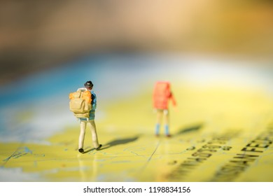 Travel Concept. Two traveler miniature figures with backpack walking on world map under sunlight.