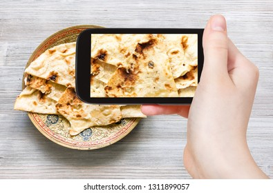 travel concept - visitor photographs of Indian cuisine of Naan flat bread baked in tandoor on brass plate on smartphone