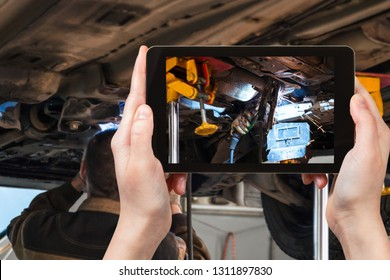 travel concept - visitor photographs of welding the silencer on car by argon welding during repairing in workshop on smartphone
