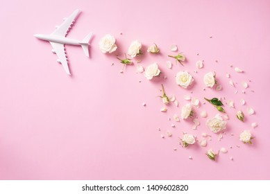 Travel concept with white plane and flowers, petals on pink background. Top view, flat lay. Copy space. Trip, vacation concept.