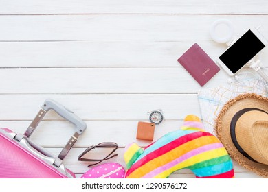 Travel concept with Women's accessories and essential travel items on white wooden board background