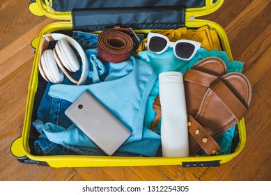 travel concept. yellow suitcase with different stuff around it. top view