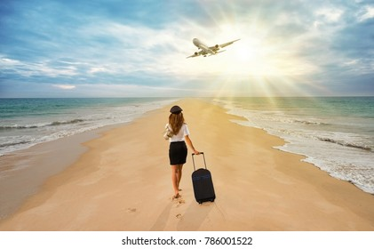 Travel concept. Young woman in office clothes walking on the beach with suitcase and hat . Overhead fly plane.