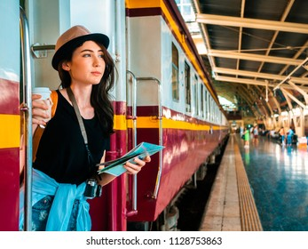 travel concept.beautiful traveller girl in train station.beautiful woman wear hat holding coffee cup and map on train.copy space train station platform background.