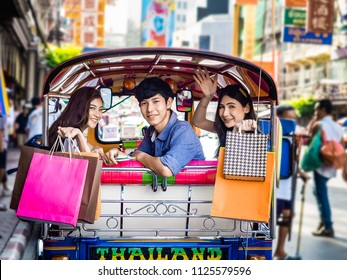 travel concept.group of happy friend are traveling.tourist holding shopping bag sitting in tuk tuk thai traditional taxi with blurring china town bangkok background.