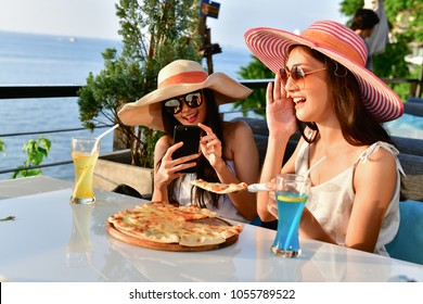 Travel Concepts. Beautiful girl is eating at a seaside restaurant. Asian girls come to relax at the beach restaurant. Asian girls enjoy eating at the beach restaurant.