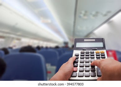 Travel cost calculation concept by calculator and airplane's cabin in background