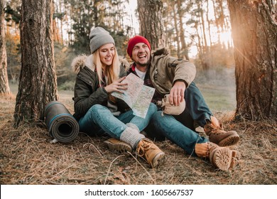 Travel couple camping with map having fun in the forest. Concept of trekking, adventure and seasonal vacation.