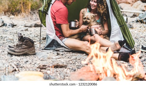 Travel couple camping in rock mountains with their dog - Climber people drinking hot tea inside tent next bonfire - Sport, nature life, love and vacation concept - Main focus on girl face