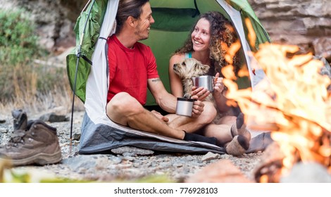 Travel couple camping in rock mountains with their dog - Climber people drinking hot tea inside tent next bonfire - Sport, nature life, love and vacation concept - Main focus on man face