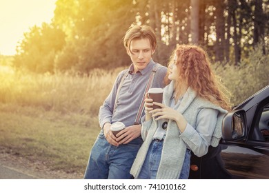 Travel. Couple drinking coffee and relaxing on the roadside