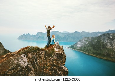 Travel couple enjoying view together on cliff edge in Norway man and woman family healthy traveling lifestyle summer vacations outdoor success friendship happy emotions