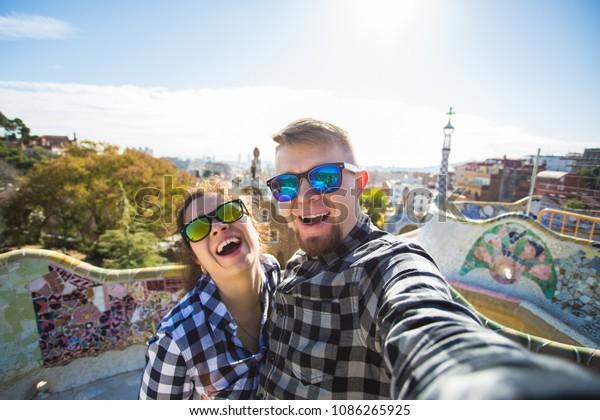Viajero feliz haciendo un retrato de selfie con smartphone en Park Guell, Barcelona, España. Hermosa pareja joven mirando la cámara tomando una foto con el teléfono inteligente sonriendo enamorados