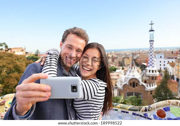 Travel couple happy talking selfie self-portrait with smartphone in Park Guell, Barcelona, Spain. Beautiful young multiracial couple looking at camera taking photo with smart phone smiling in love.