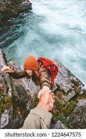 Travel couple helping hand holding together on rocks over river man and woman family adventure lifestyle vacations outdoor exploring wilderness
