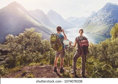 travel, couple of hikers with backpacks relaxing and taking photos during trek on top of the mountain