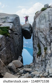 Travel couple in love on Kjeragbolten romantic trip in Norway Kjerag mountains vacations adventure lifestyle family man and woman together extreme journey concept.
