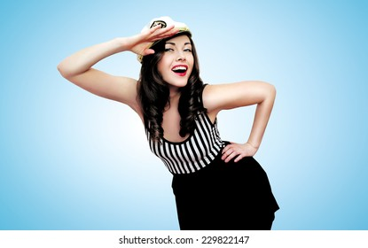 Travel, cruise, people concept - pretty smiling woman brunette sailor saluted in pin-up style over blue background