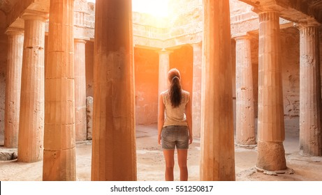 Travel Cyprus - Back view of young woman standing between columns in ancient temple ruins on Cyprus. Tomb raider searching for a treasure