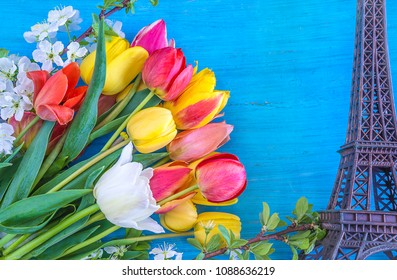 Travel destination concept: effel tower and bouquet of multicolored tulips on blue wooden background