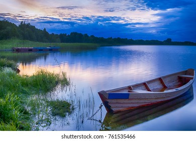 Travel Destinations Concepts. Peaceful Picturesque Landscape of The Strusto Lake with Wooden Boat at Foreground. Lake is a Part of National Braslav Lakes Reserve. Horizontal Image Orientation