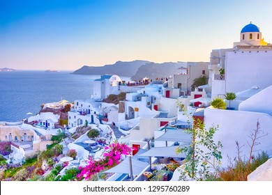 Travel Destinations. People Preparing for Sunset at Caldera Volcanic Slope of Oia Village in Santorini Island in Greece. Horizontal Image Composition