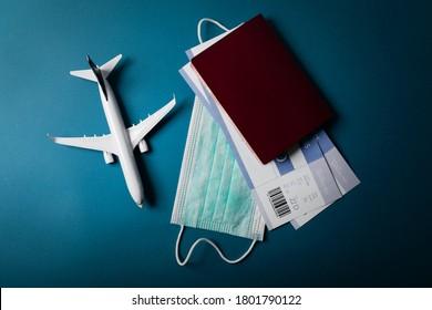 Reisen während der Covid-19-Pandemie. Flugzeugmodell mit Gesichtsmaske und Reisedokumenten