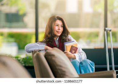 Travel, Education, Tourism and People - Smiling Asian woman with luggage and holding book, passport at airport.