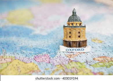 Travel and educational concept. Tourist attractions and souvenir of Oxford on background map of the world of puzzles for travelers