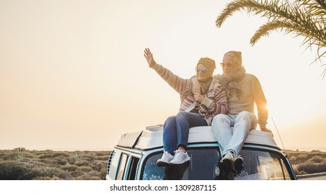 Travel and enjoying life lifestyle in love for couple in relationship sitting on the roof of a old vintage romantic van with sunset and sunlight golden tones background - forever together