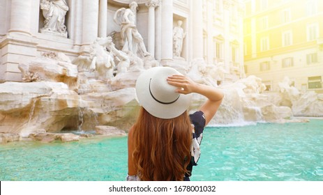 Travel in Europe. Beautiful young woman visiting Trevi Fountain in Rome, Italy. Happy girl enjoying Italian holidays in summer.