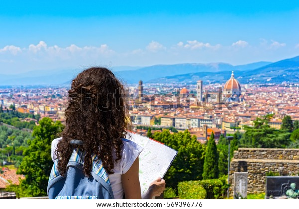 Travel to Europe. Happy Tourist in Florence traveling. Cheerful Young brunette Woman traveler with Map over Cathedral of Santa Maria del Fiore (Duomo). Florence is popular travel place in Italy.