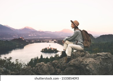 Travel Europe. Traveler woman in hat with backpack exploring Slovenia. Young hiker girl enjoying breathtaking view on amazing Bled Lake with Island and Alps Mountain. Autumn or winter nature landscape