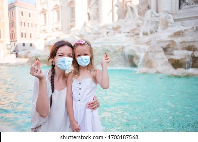 Travel family mom and girl wearing a mask for prevent virus and trowing coin at Trevi Fountain, Rome, Italy for good luck. Happy family making a wish to come back.
