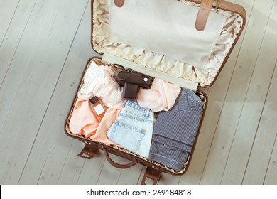Travel: female brown suitcase with clothes for travel