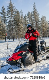 Travel to Finland. Winter fairy tale in a sunny frosty day. The first trip on snowmobiles in special suits. The concept of active and extreme tourism