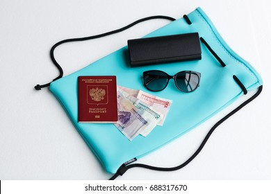 Travel flat lay: passport, sunglasses, case, money, backpack lying on white background